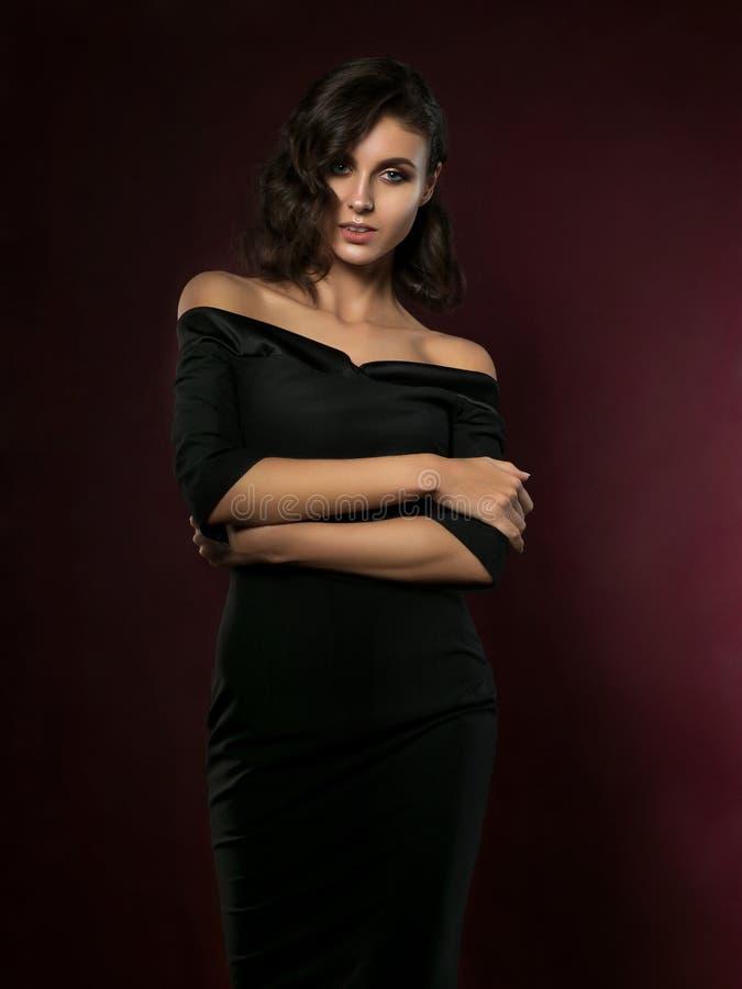 Junge Schönheit, die schwarzes Abendkleid trägt stockbilder