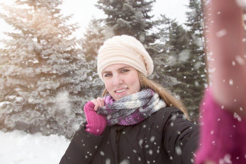 Junge Schönheit, die selfie über Winterhintergrund nimmt r lizenzfreie stockfotografie