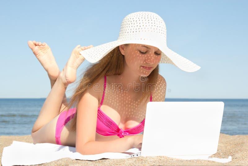 Junge Schönheit, die an weißem Laptop am Strand arbeitet stockfotos