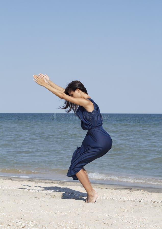 Junge Schönheit, die Yoga an der Küste im blauen Kleid tut lizenzfreies stockbild