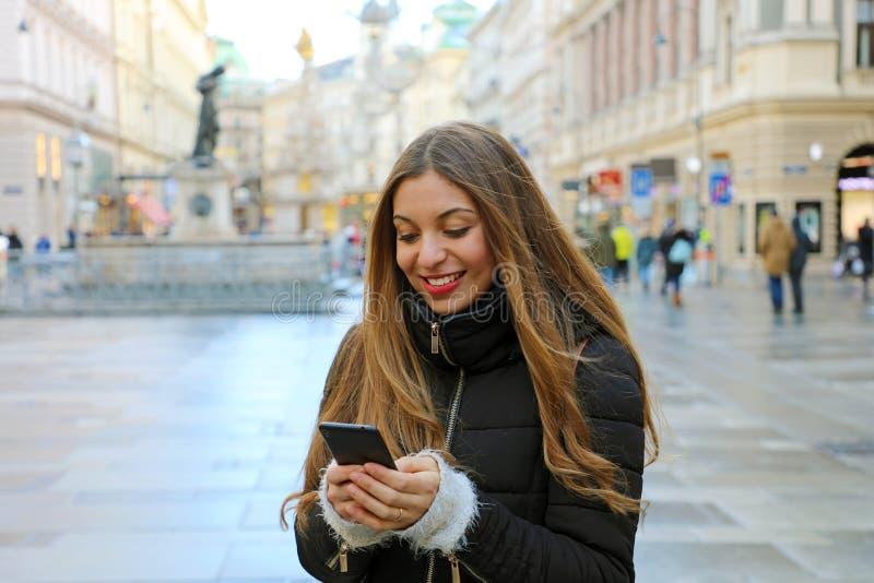 Junge Schönheit, die zufällige Winterkleidung unter Verwendung des Telefons im Freien in der europäischen Stadt trägt Mädchen mit stockbild