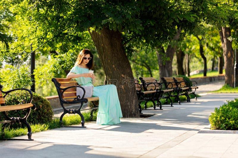 Junge Schönheit in einem hellgrünen langen Pastellkleid ist sitt lizenzfreie stockfotos