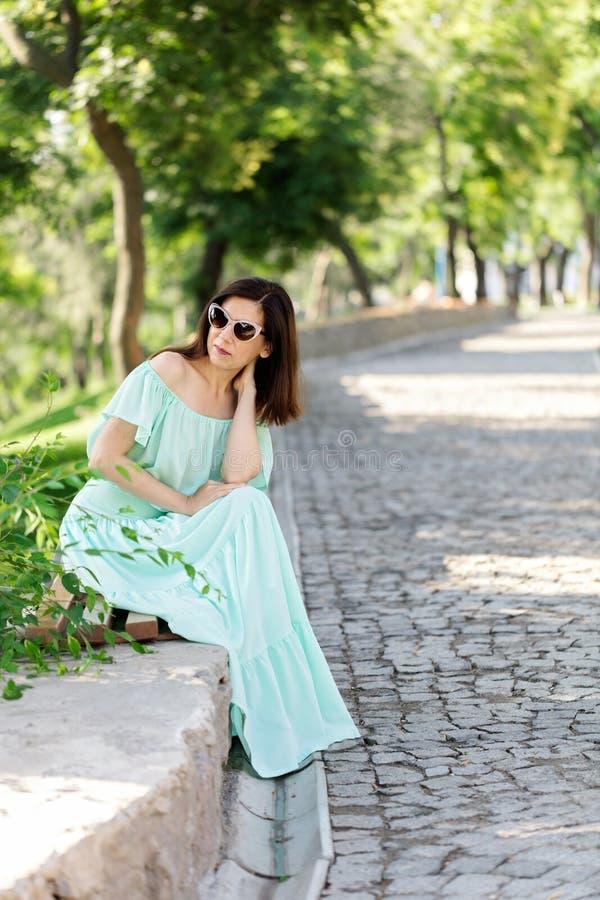 Junge Schönheit in einem hellgrünen langen Pastellkleid ist sitt lizenzfreies stockfoto