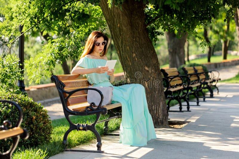 Junge Schönheit in einem hellgrünen langen Pastellkleid ist sitt stockbild