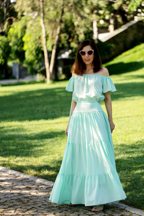 Junge Schönheit in einem hellgrünen langen Pastellkleid ist Weg stockfotografie