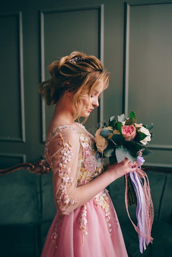 Junge Schönheit in einem rosa Kleid, das in einem Weinleseraum steht lizenzfreies stockfoto
