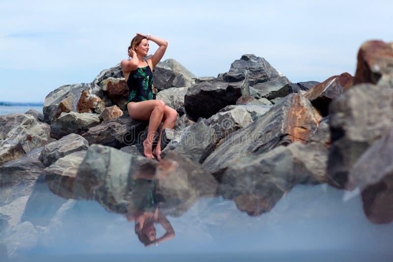 Junge Schönheit in einem schwarzen Badeanzug stockfotografie