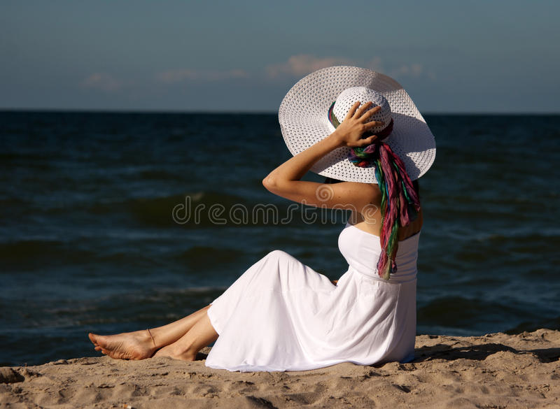Junge Schönheit in einem weißen Kleid auf dem Strand lizenzfreie stockfotos