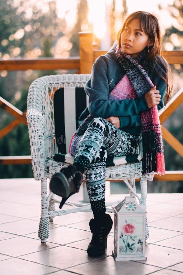 Junge Schönheit in einer blauen Strickjacke mit dem bunten Schal, der auf einem weißen Stuhl bei kühlem Wetter außerhalb des Balk stockfoto