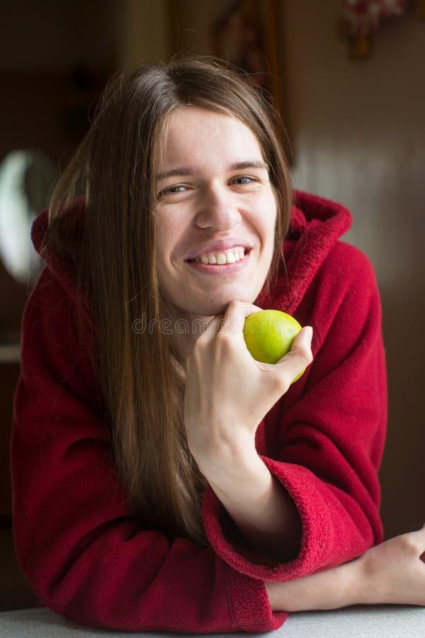 Junge Schönheit in einer roten Jacke mit dem langen Haar, das den Handapfel hält lizenzfreie stockbilder