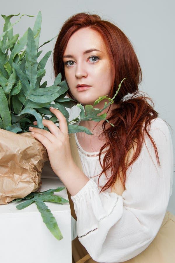 Junge Schönheit hat rotes Haar, das kreatives Gold aufwerfen in einem Studio mit Blumen bilden lizenzfreie stockfotografie