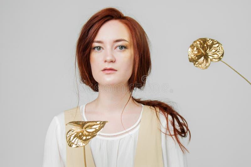 Junge Schönheit hat rotes Haar, das kreatives Gold aufwerfen in einem Studio mit Blumen bilden lizenzfreie stockfotos