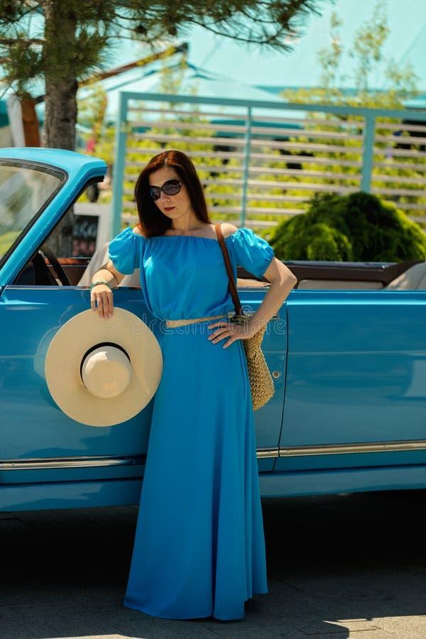 Junge Schönheit im azurblauen langen Kleid nahe einem Retro- Auto lizenzfreie stockfotos