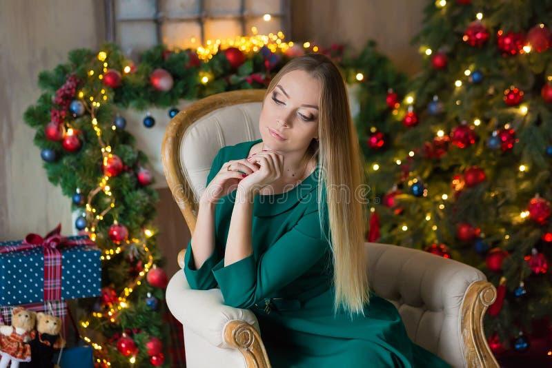 Junge Schönheit im blauen eleganten Glättungskleid, das auf Boden nahe Weihnachtsbaum und Geschenken auf Sylvesterabend sitzt inn lizenzfreie stockfotos