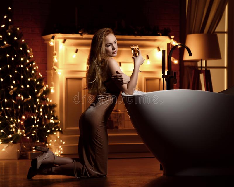 Junge Schönheit im eleganten Kleid über Weihnachtsbaum-Innenraumhintergrund stockfotos