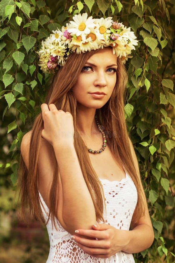 Junge Schönheit im Freien in einem birchwood tragenden wreth des Gänseblümchens lizenzfreies stockfoto