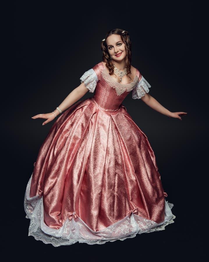 Junge Schönheit im mittelalterlichen Kleid, das Knicks auf Schwarzem macht stockfoto