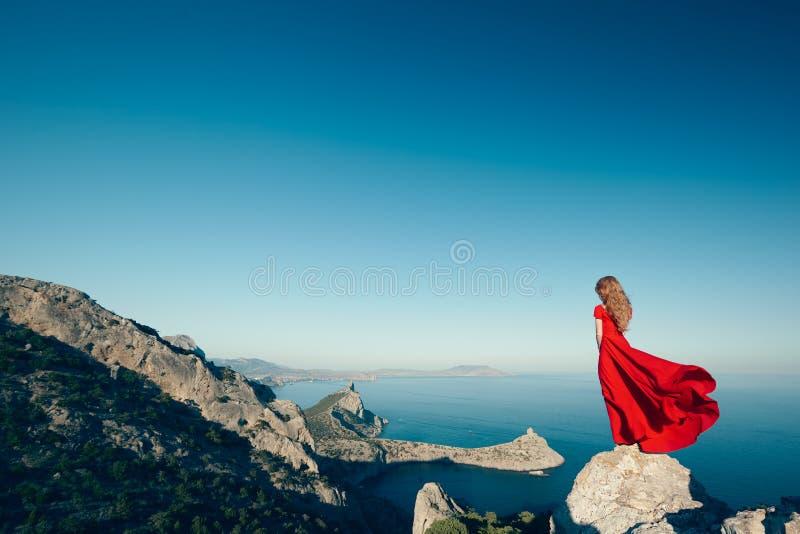 Junge Schönheit im roten Kleid, das zum Gebirgsmeer schaut stockfotografie