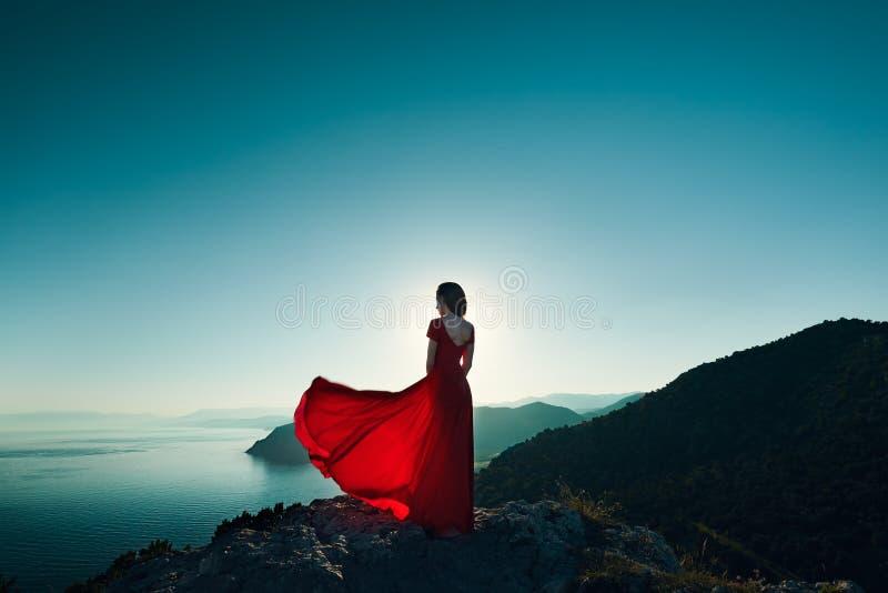 Junge Schönheit im roten Kleid, das zum Gebirgsmeer schaut lizenzfreie stockbilder