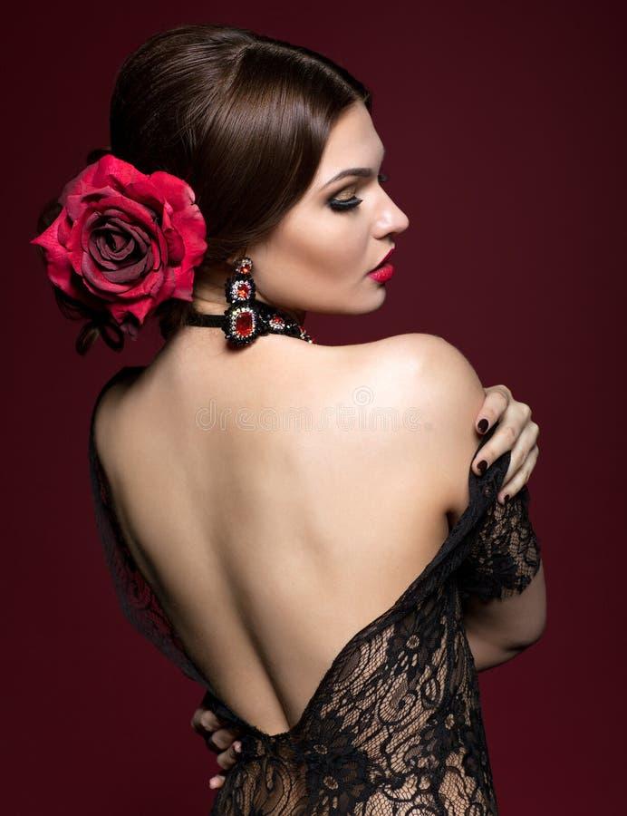 Junge Schönheit im schwarzen Kleid und Schwarzrose blühen in ha stockfotos