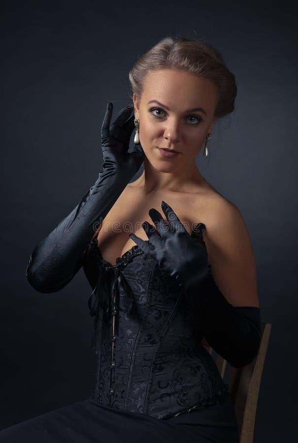 Junge Schönheit im schwarzen Korsett mit Perlenohrringen lizenzfreies stockbild