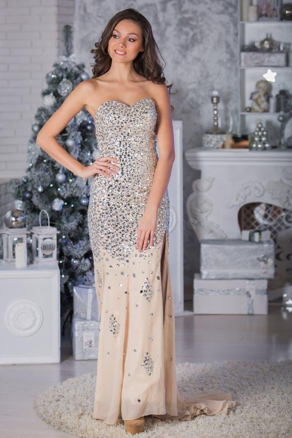 Junge Schönheit im silbernen eleganten Kleid, das im interi steht stockbild