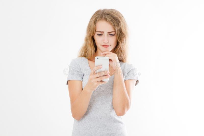 Junge Schönheit im T-Shirt unter Verwendung ihres Smartphone lokalisiert auf weißem Hintergrund blondes Mädchen, das mit Freund o lizenzfreie stockfotografie