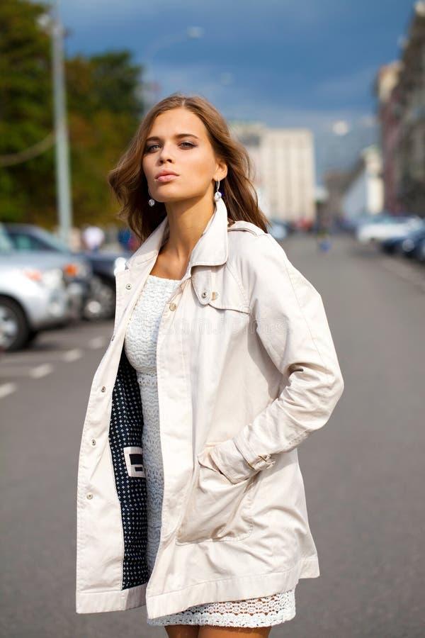 Junge Schönheit im weißen Mantel stockfoto