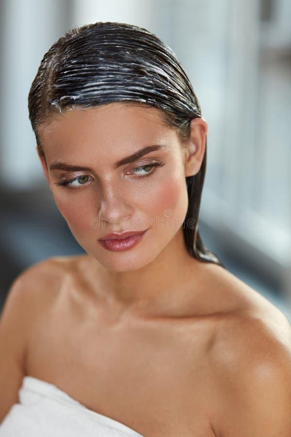 Junge Schönheit mit angewandter natürlicher Haar-Maske Junges asiatisches Mädchen, das Haar mit dem Finger getrennt auf weißem Hi lizenzfreie stockfotografie