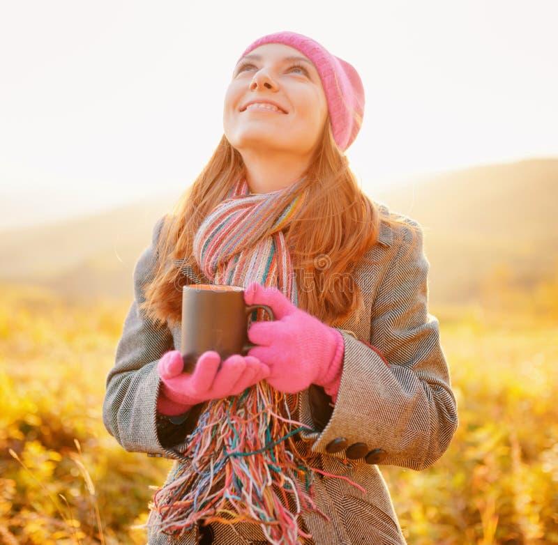 Junge Schönheit mit dem Becher in der Hand, der den Herbsthimmel betrachtet stockfoto