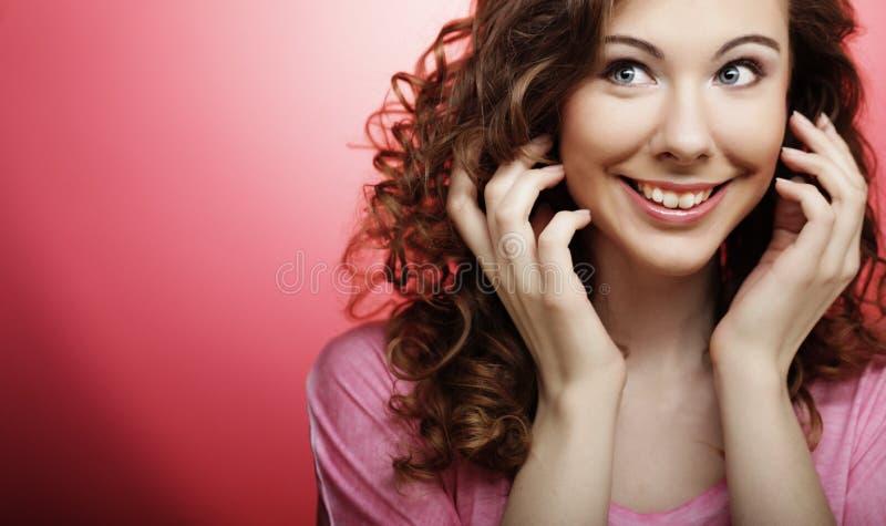 Junge Schönheit mit dem gelockten Haar über rosa Hintergrund stockfotos