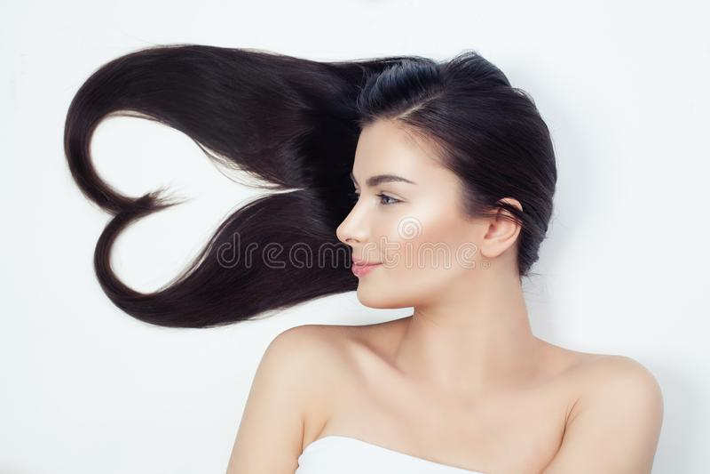 Junge Schönheit mit dem gesunden gelockten Haar Herz des Haares, Haarpflegekonzept lizenzfreies stockfoto