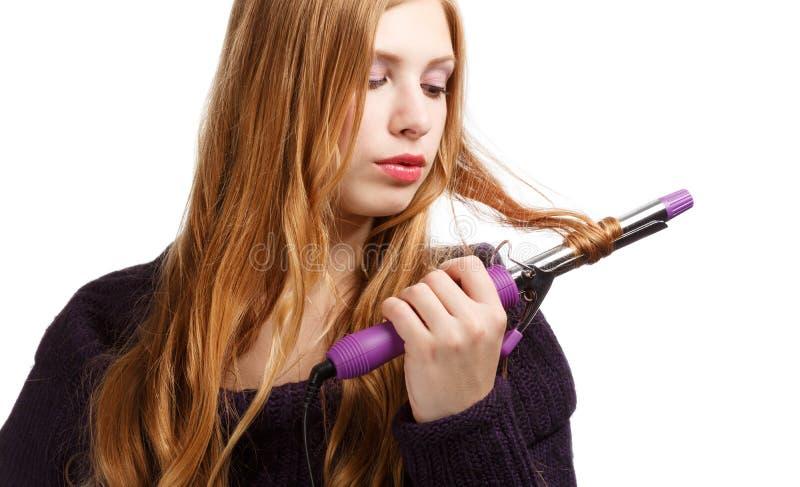 Junge Schönheit mit dem langen blonden Haar, das ihre Verschlüsse wi anredet stockfotos