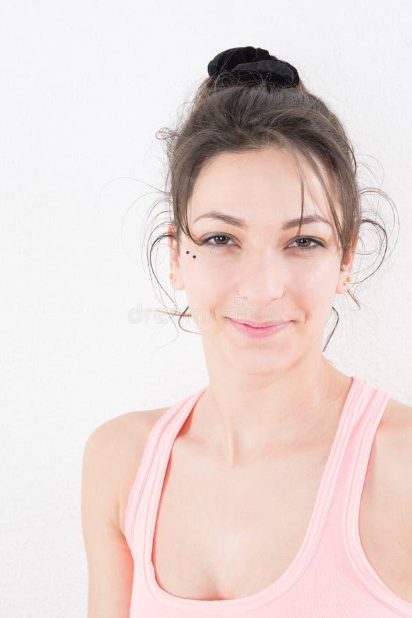 Junge Schönheit mit dem langen Brunettehaar, das gegen weißen Hintergrund aufwerfen und dem Mädchen, das Sie betrachtet lizenzfreies stockfoto