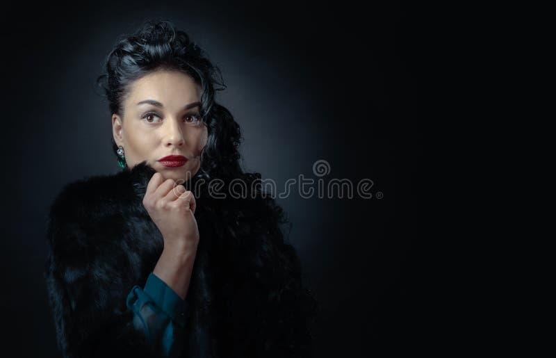 Junge Schönheit mit dem langen gelockten Haar im schwarzen Pelzmantel lizenzfreie stockfotografie
