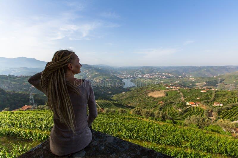 Junge Schönheit mit den blonden Dreadlocks, die auf der Betrachtungsplattform gegenüber von Weinbergen sitzen, sind auf Hügel an  stockfotografie