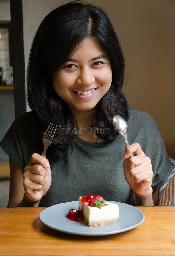 Junge Schönheit mit einem Kuchen im Café lizenzfreie stockfotos