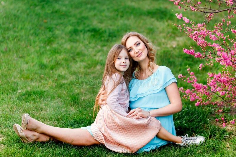 Junge Schönheit mit einer kleinen Tochter, die durch die blühende Kirschblüte geht Das Konzept des Familienrestes und -liebe stockfotografie