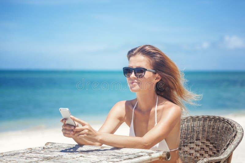 Junge Schönheit mit Handy auf dem Ufer des trop stockbild