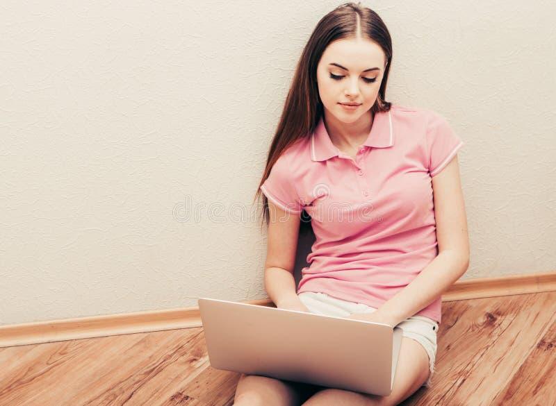 Junge Schönheit mit Laptopnotizbuch auf surfendem Hauptinternet des Bodens lizenzfreie stockbilder
