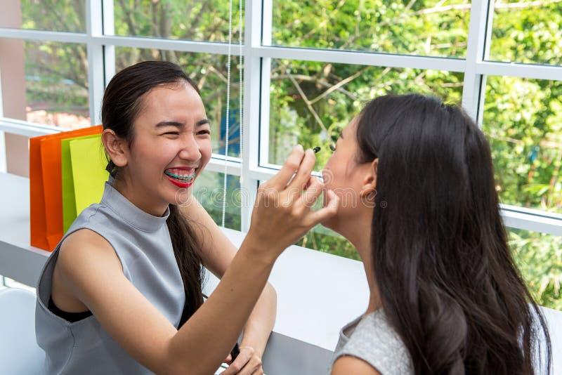Junge Schönheit mit Make-upbürste Zwei Freunde, die i bilden lizenzfreie stockfotos