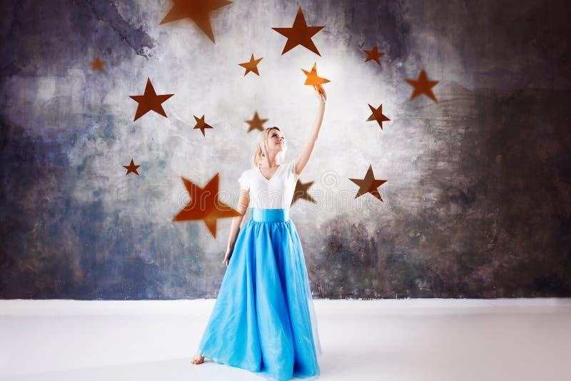 Junge Schönheit nahm einen Stern vom Himmel Fantasiekonzept, Reichweite für den Traum stockbilder