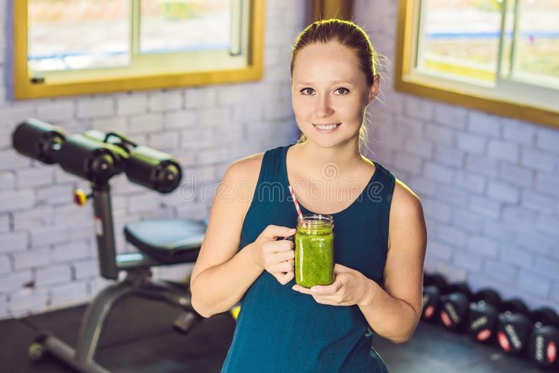 Junge Schönheit trinkender Gemüsesmoothie nach Eignung zu Hause und Lächeln Eignung und gesunder Lebensstil lizenzfreie stockfotos