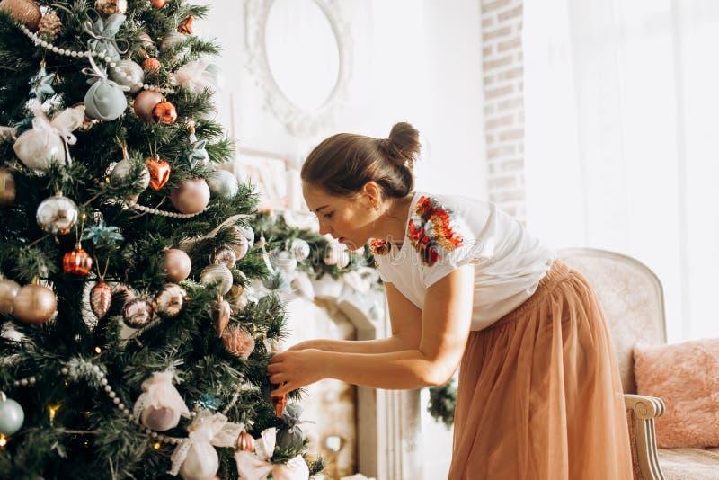 Junge Schönheit verziert einen Baum des neuen Jahres im vollen des hellen gemütlichen Raumes lizenzfreies stockfoto