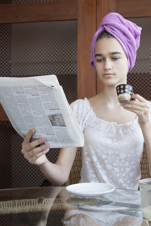 Junge Sch?nheit, welche zu Hause die Zeitung liest und Kaffee trinkt lizenzfreie stockfotografie