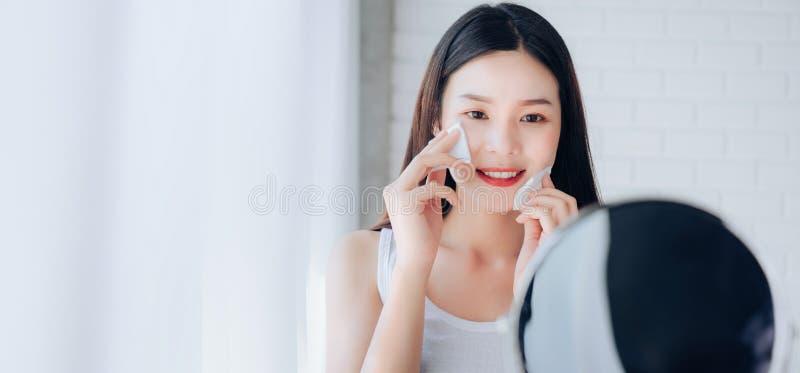 Junge Schönheits-Asiatin-Reinigungsgesicht mit Baumwolle sie Spiegel betrachtend stockfoto