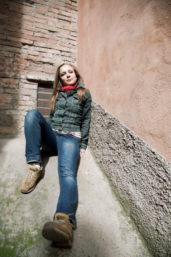 Junge Schönheits-Frau, die auf Betonmauer legt stockfotografie