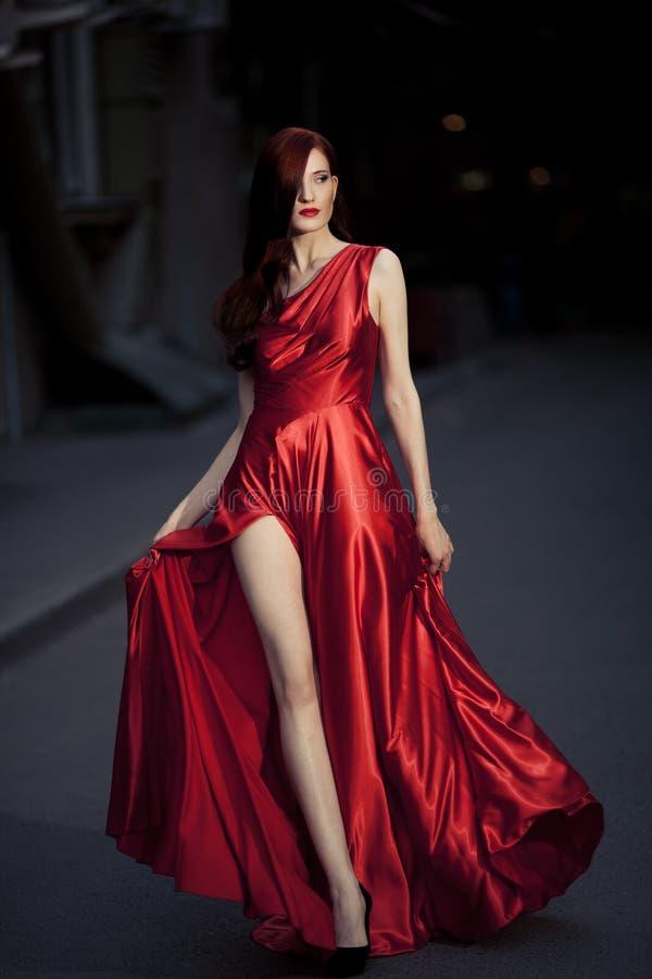 Junge Schönheits-Frau in flatterndem rotem Kleid lizenzfreie stockbilder