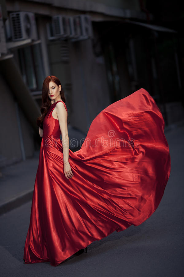 Junge Schönheits-Frau im roten Kleid im Freien lizenzfreies stockbild