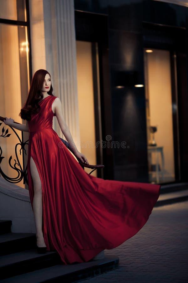 Junge Schönheits-Frau im roten Kleid im Freien stockfotografie